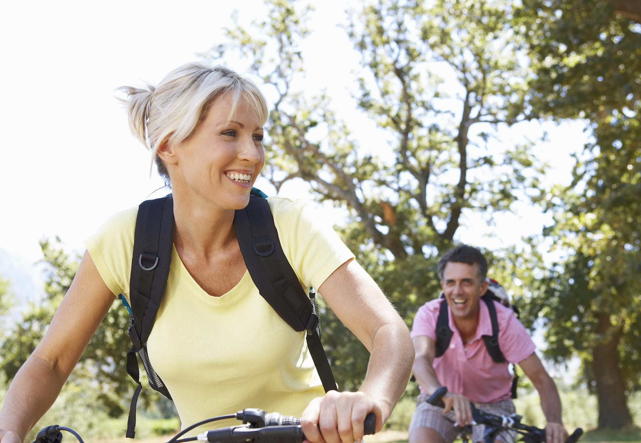 Man and woman biking after seeing denture specialists